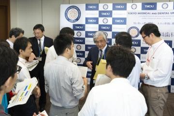 情報交換会でメディア関係者から囲み取取材を受ける横関教授と宮﨑教授